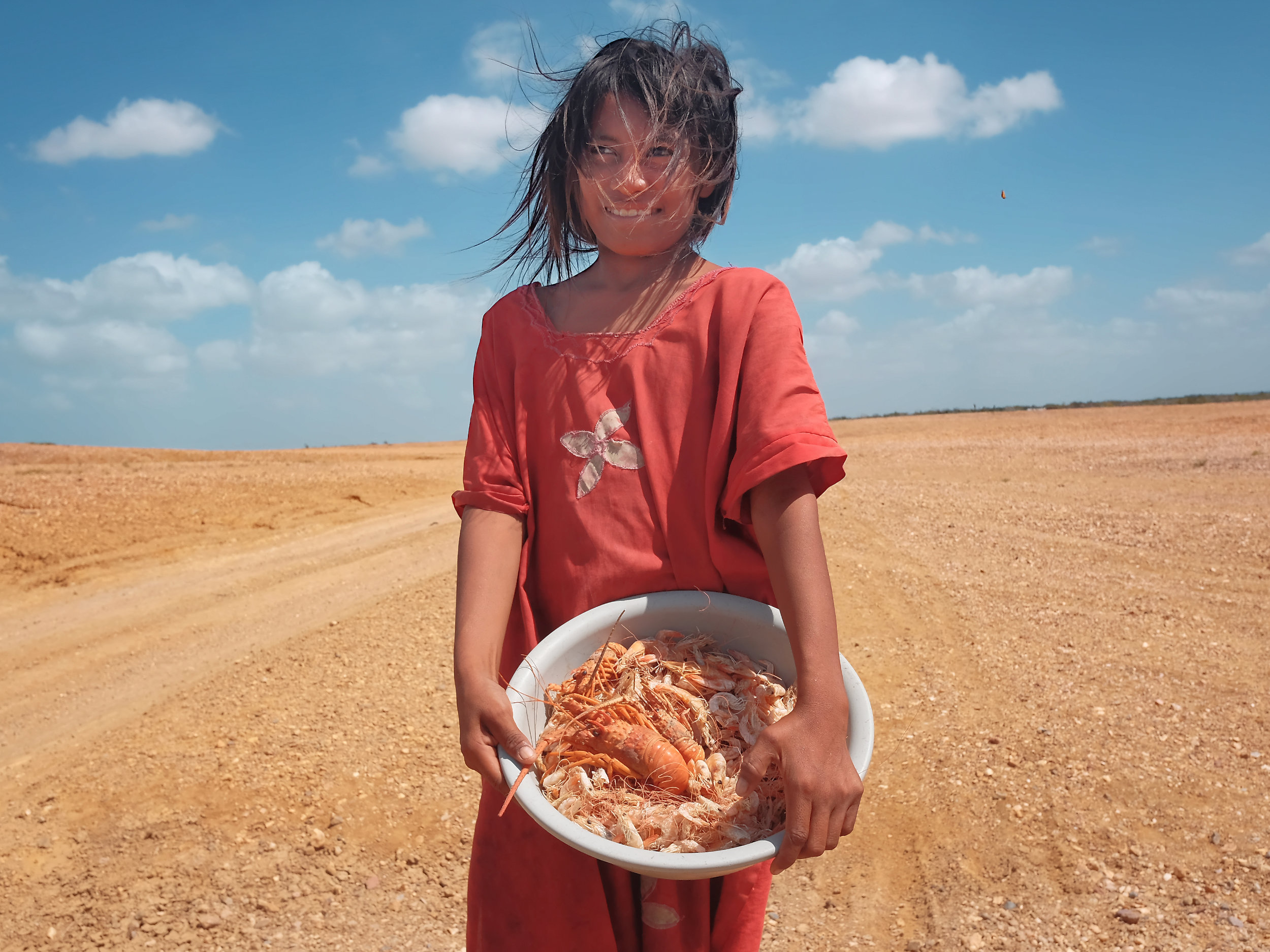 A Wayuu girl with a bowl of shrimps